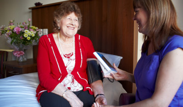 Bridge House resident has her blood pressure taken