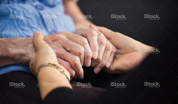 A younger person holding hands with an elderly person for comfort
